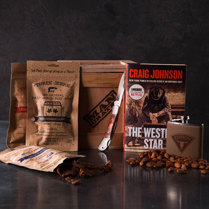 Storied Western Cocktail Crate includes a Longmire novel by Craig Johnson, personalized flask, an assortment of jerky, lockback pocketknife, and almonds.