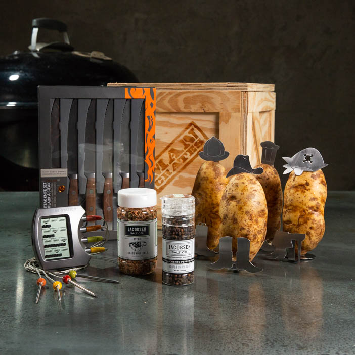 Steaks On A Plate Crate includes a steak knife set, seasoning salts, digital steak thermometer, and decorative potato accessories.