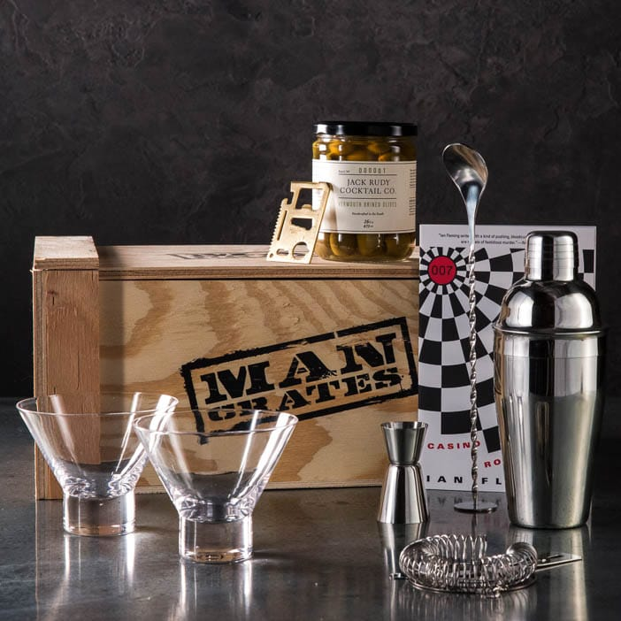 Storied Spy Cocktail Crate includes Casino Royale by Ian Fleming, brined olives, martini glasses, cocktail shaker, jigger, pourer, recipe book, and a credit card tool.