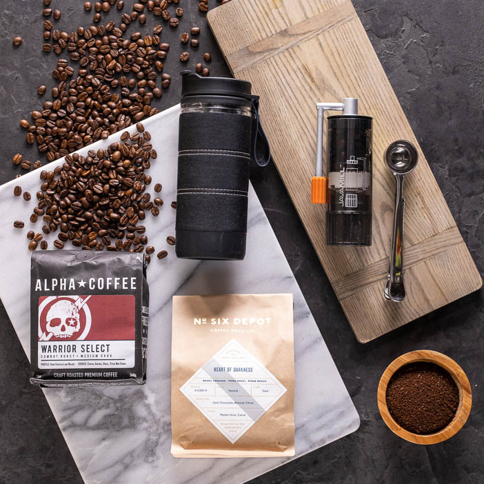 Coffee tumbler, grinder, spoon, and two bags of beans for a great men's drink gift.
