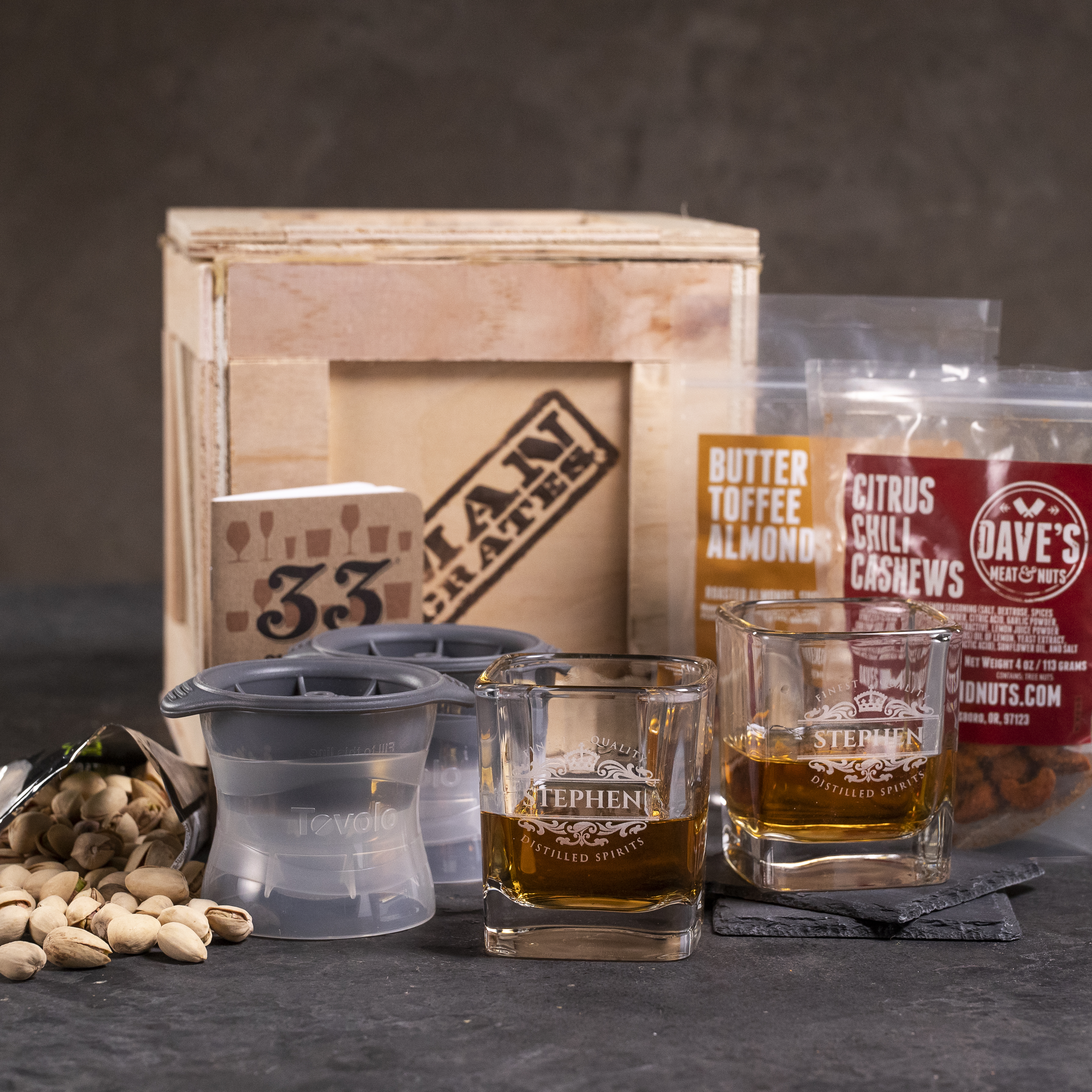 Front view of personalized glassware, snacks, and ice molds with a crate.