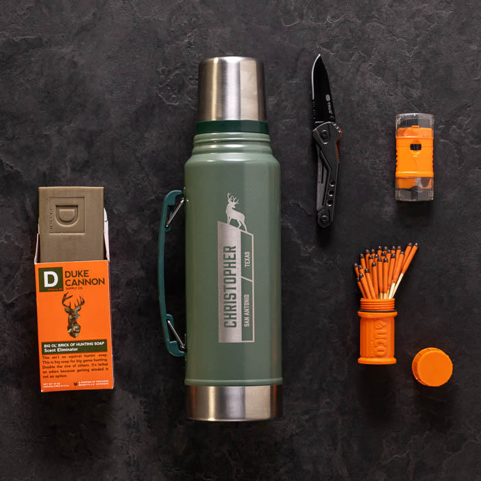 Overhead of knife, matches, soap, and personalized travel thermos for a great men's outdoor gift.