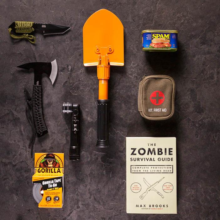 Knife, axe, shovel, flashlight, spam, duct tape, medical kit, and zombie survival book for men's interest gift.
