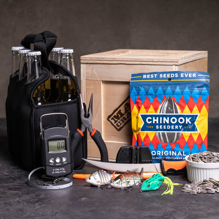 Bass Whisperer Crate includes an assortment of bass lures, an insulated 6-pack cooler, portable scale, needle nose pliers, and sunflower seeds.