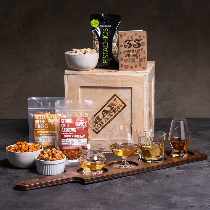 Whiskey glasses on paddle, nuts in bowls, journal, and a crate for a great men's whiskey gift.